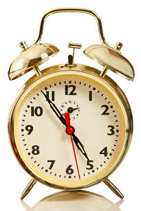 Golden alarm clock - isolated over a white background