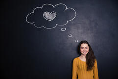 Beautiful happy young woman thinking about love and standing with blackboard behind her