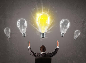 Business person having an bright idea from idea generation and structured innovation - light bulb concept