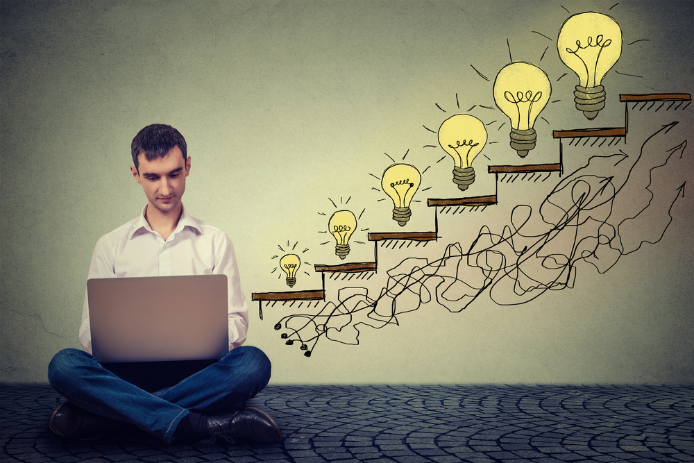 Young man sitting on the floor with lightbulbs of increasing sizes on the wall next to him. Representing structured innovation - ideas must be struggled to improve.